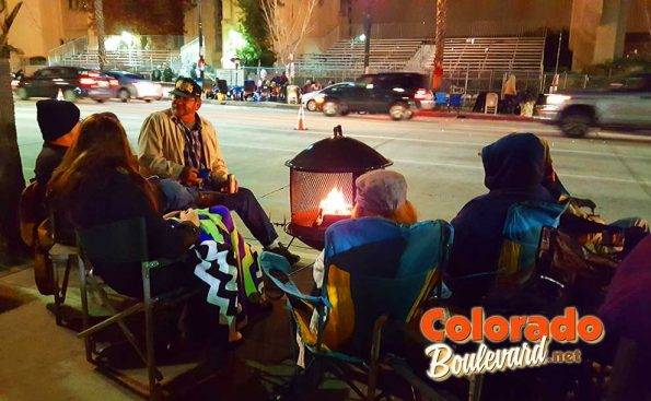 People huddled by the fire on the street