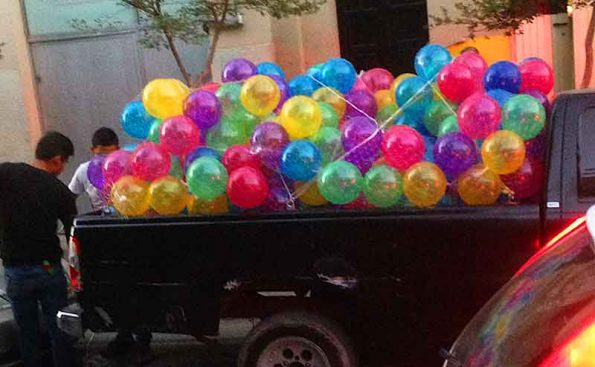 bunch of balloons on tthe bed of a truck